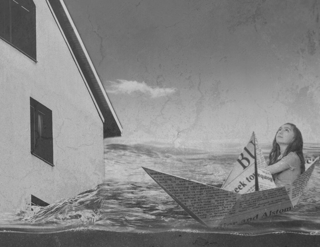 A girl sitting in a paper boat looks up at a clear sky; at left, a house looms, seeming to slip into the sea.